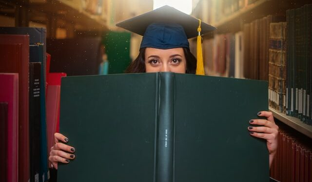 Female grad school student holding a big book in a library