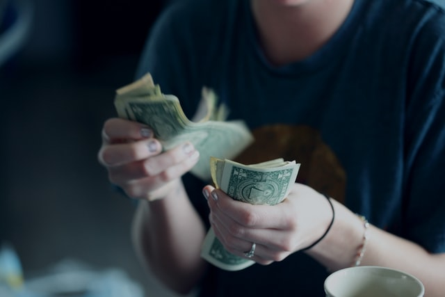 Woman counting dollar notes