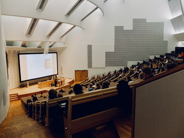 A grad school classroom full of college students listening to a lecture