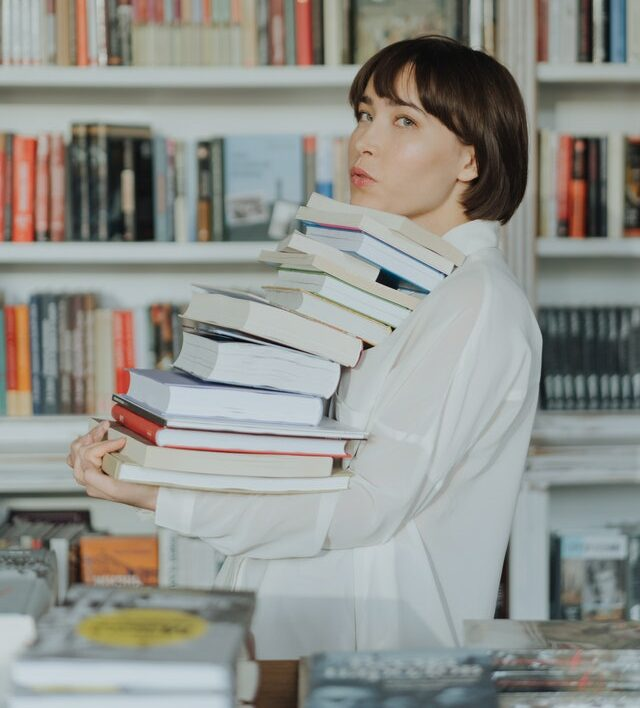 person holding large stack of books